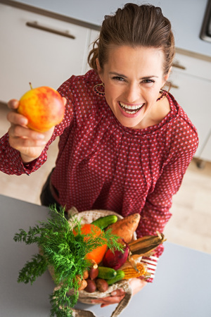 cradling: Take a bite, I promise it is delicious... An elegant woman is laughing and teasing in a kitchen, holding up colourful apple and cradling a burlap sac of fresh fall vegetables bought at the market.