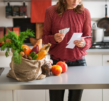 And thus, having completed her shopping for fresh autumn vegetables, a woman reads her shopping lists and holds her leftover cash. On the kitchen counter, a burlap sac holds her fresh produce.