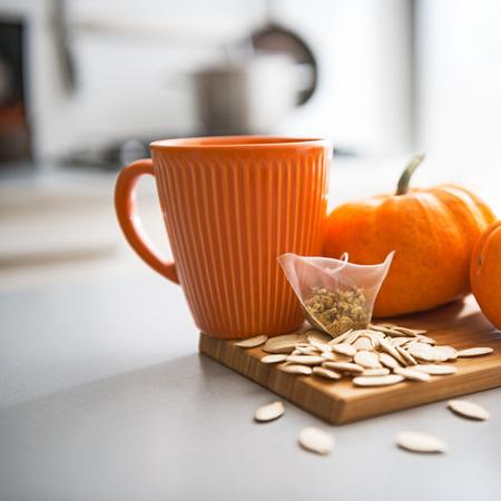 Closeup on small pumpkins seeds and tea bag on table
