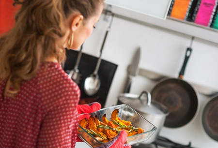 Young housewife holding baked pumpkin. rear view Stock Photo