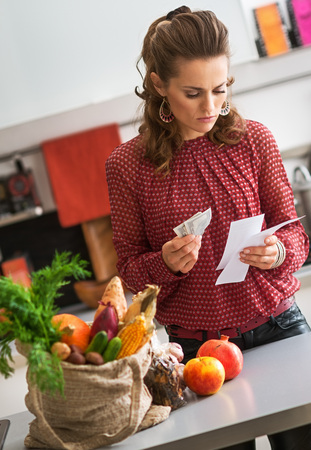 burlap sac: And thus, having completed her shopping for fresh autumn vegetables, a woman reads her shopping lists and holds her leftover cash. On the kitchen counter, a burlap sac holds her fresh produce.