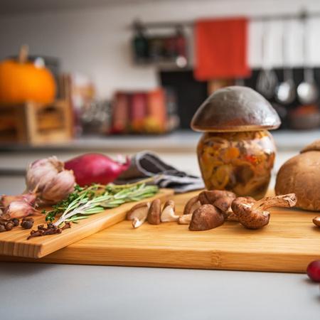 Closeup on jar of pickled mushroom on cutting board