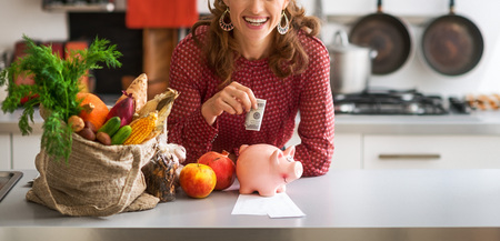 Closeup on happy young housewife putting money into piggy bank after shopping on local market Stock Photo