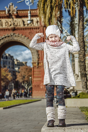 in Barcelona for a perfect winter. Full length portrait of happy trendy child near Arc de Triomf in Barcelona, Spain showing strength