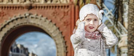 in Barcelona for a perfect winter. Full length portrait of trendy girl near Arc de Triomf in Barcelona, Spain holding her hat