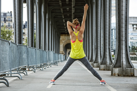 Outdoors fitness in Paris. Seen from behind young active woman stretching on Pont de Bir-Hakeim bridge in Paris Stock Photo