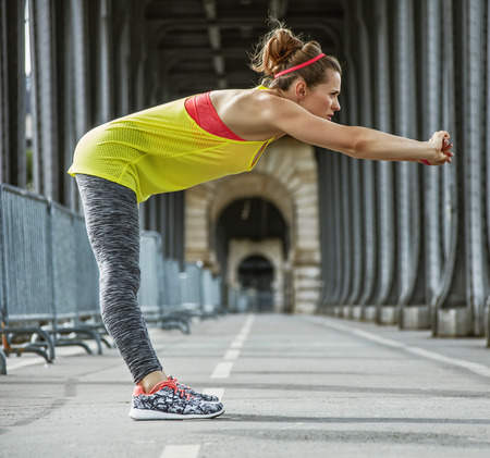 Outdoors fitness in Paris. Full length portrait of young active woman stretching on Pont de Bir-Hakeim bridge in Paris Stock Photo