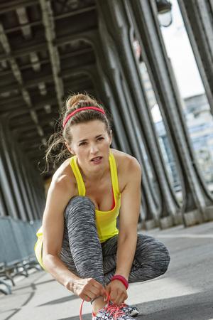Outdoors fitness in Paris. young woman jogger tying shoelaces on Pont de Bir-Hakeim bridge in Paris