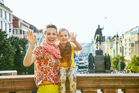 mam: The spirit of old Europe in Prague. happy young mother and daughter tourists on Wenceslas Square in Prague, Czech Republic handwaving Stock Photo