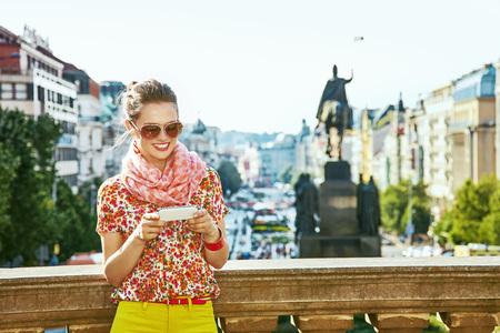 The spirit of old Europe in Prague. happy modern traveller woman on Vaclavske namesti in Prague, Czech Republic writing sms