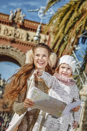 mam: in Barcelona for a perfect winter. Portrait of happy modern mother and child near Arc de Triomf in Barcelona, Spain holding map and pointing