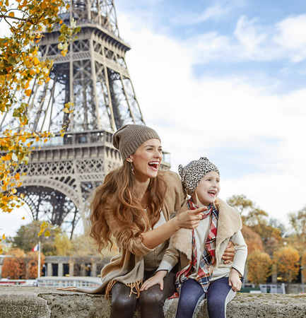 mam: Autumn getaways in Paris with family. happy mother and daughter tourists on embankment in Paris, France pointing on something while sitting on the parapet