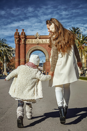 in Barcelona for a perfect winter. Seen from behind modern mother and daughter in Barcelona, Spain walking
