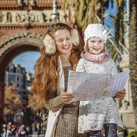 mam: in Barcelona for a perfect winter. smiling modern mother and daughter near Arc de Triomf in Barcelona, Spain looking at the map Stock Photo
