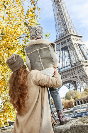 Autumn getaways in Paris with family. Seen from behind mother and child travellers on embankment in Paris, France looking on Eiffel Tower
