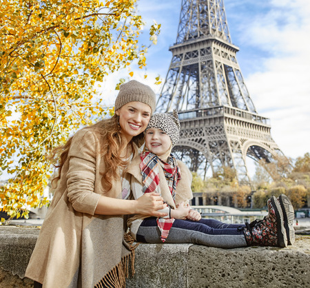 mam: Autumn getaways in Paris with family. Portrait of smiling mother and daughter travellers on embankment near Eiffel tower in Paris, France sitting on the parapet