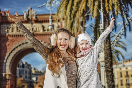 in Barcelona for a perfect winter. Portrait of happy modern mother and child in Barcelona, Spain rejoicing
