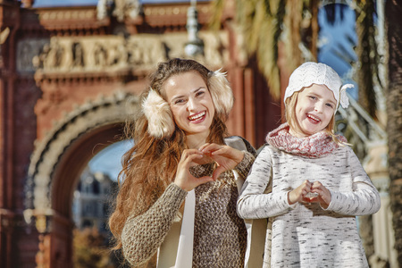 in Barcelona for a perfect winter. Portrait of smiling trendy mother and child in Barcelona, Spain showing heart shaped hands