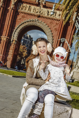 in Barcelona for a perfect winter. Portrait of happy young mother and child near Arc de Triomf in Barcelona, Spain handwaving