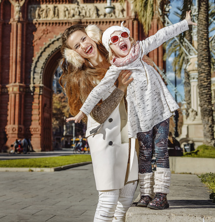mam: in Barcelona for a perfect winter. Portrait of smiling trendy mother and daughter near Arc de Triomf in Barcelona, Spain having fun time