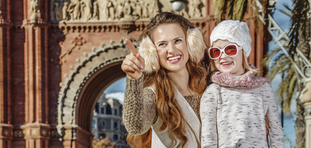 mam: in Barcelona for a perfect winter. Full length portrait of smiling modern mother and child near Arc de Triomf in Barcelona, Spain pointing on something Stock Photo