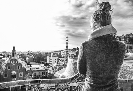 Barcelona signature style. Seen from behind trendy woman in coat at Guell Park in Barcelona, Spain Stock Photo