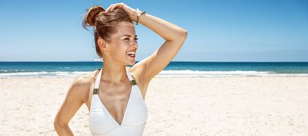 Heading to white sand blue sea paradise. Happy woman in white swimsuit at sandy beach on a sunny day looking aside Stock Photo