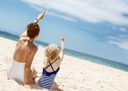 Family fun on white sand. Seen from behind mother and child in swimsuits sitting at sandy beach on a sunny day and pointing up on something