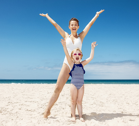 mam: Family fun on white sand. Happy mother and child in swimsuits at sandy beach on a sunny day rejoicing