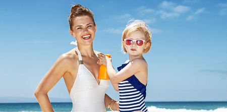Family fun on white sand. Child applying sunscreen on smiling mother in swimsuit at sandy beach on a sunny day