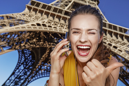 mobile communication: Touristy, without doubt, but yet so fun. happy young woman showing thumbs up and speaking on a mobile phone against Eiffel tower in Paris, France Stock Photo