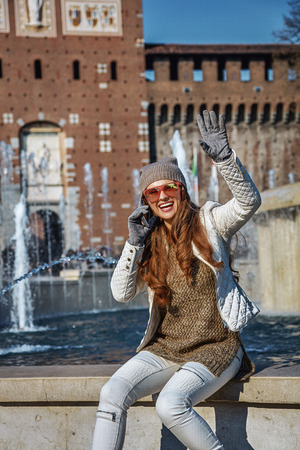 sforza: Rediscovering things everybody love in Milan. smiling young traveller woman near Sforza Castle in Milan, Italy speaking on a smartphone and handwaving