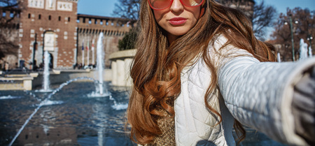 sforza: Rediscovering things everybody love in Milan. trendy woman near Sforza Castle in Milan, Italy taking selfie