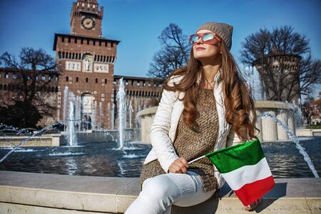 sforza: Rediscovering things everybody love in Milan. young traveller woman near Sforza Castle in Milan, Italy with Italian flag Stock Photo