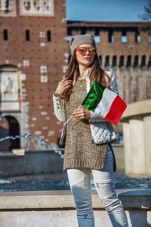 everybody: Rediscovering things everybody love in Milan. young tourist woman near Sforza Castle in Milan, Italy with Italian flag looking into the distance Stock Photo
