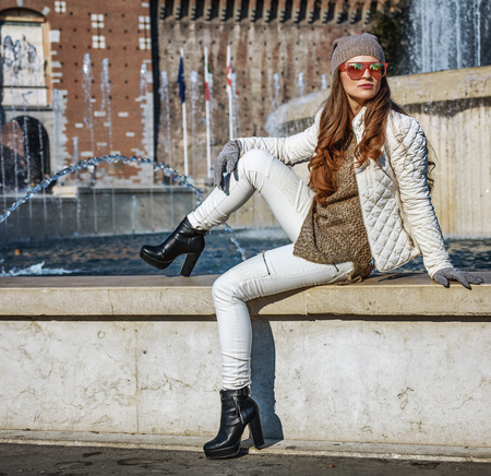 everybody: Rediscovering things everybody love in Milan. Full length portrait of modern woman in Milan, Italy sitting near fountain