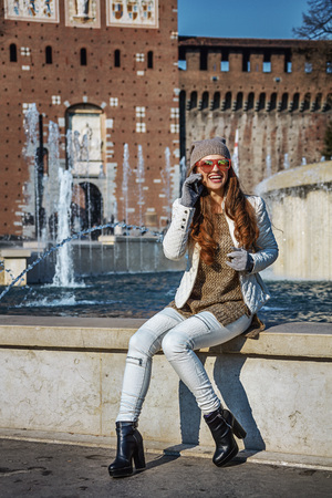 everybody: Rediscovering things everybody love in Milan. Full length portrait of smiling young traveller woman near Sforza Castle in Milan, Italy using a mobile phone Stock Photo