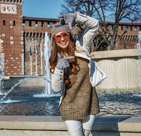 everybody: Rediscovering things everybody love in Milan. smiling young woman near Sforza Castle in Milan, Italy with hands framing