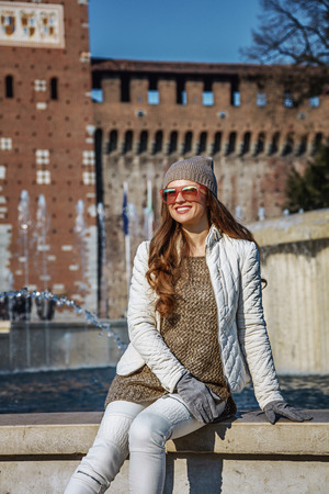 sforzesco: Rediscovering things everybody love in Milan. smiling trendy woman in front of Sforza Castle in Milan, Italy sitting near fountain