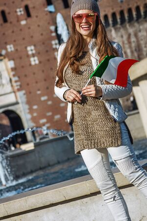 sforza: Rediscovering things everybody love in Milan. smiling young traveller woman near Sforza Castle in Milan, Italy with Italian flag