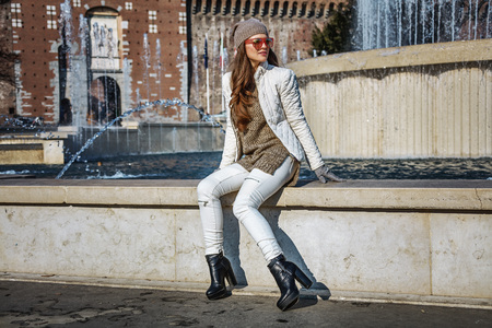 sforza: Rediscovering things everybody love in Milan. Full length portrait of young woman near Sforza Castle in Milan, Italy looking into the distance while sitting near fountain