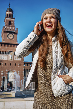 sforzesco: Rediscovering things everybody love in Milan. smiling trendy traveller woman near Sforza Castle in Milan, Italy speaking on a cell phone