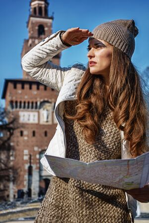 sforzesco: Rediscovering things everybody love in Milan. trendy traveller woman near Sforza Castle in Milan, Italy with map looking into the distance Stock Photo