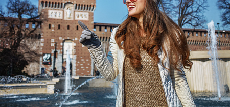 sforza: Rediscovering things everybody love in Milan. happy trendy tourist woman near Sforza Castle in Milan, Italy pointing on something