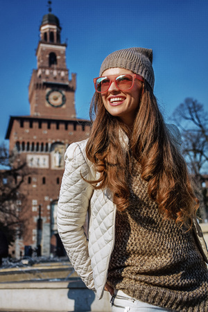 sforza: Rediscovering things everybody love in Milan. smiling young woman near Sforza Castle in Milan, Italy looking aside