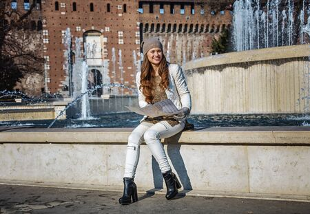 sforza: Rediscovering things everybody love in Milan. Full length portrait of smiling trendy woman near Sforza Castle in Milan, Italy with map
