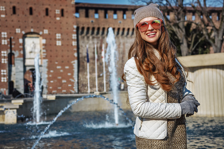 sforza: Rediscovering things everybody love in Milan. smiling young woman near Sforza Castle in Milan, Italy looking into the distance