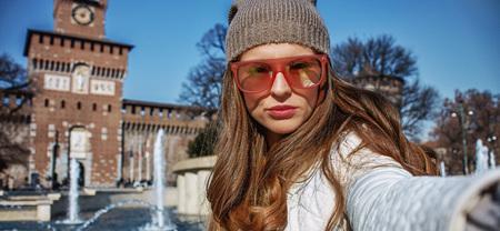everybody: Rediscovering things everybody love in Milan. trendy woman near Sforza Castle in Milan, Italy taking selfie