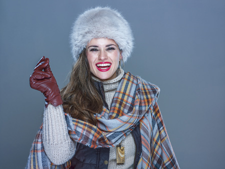 Winter things. Portrait of smiling trendy woman in fur hat isolated on cold blue snapping fingers