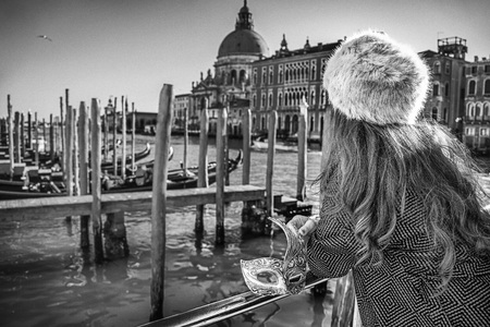 Another world vacation. Venetian mask in hand of woman in fur hat in Venice, Italy. Seen from behind
